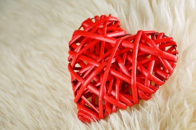 Ein aus weiden geflochtenes rotes herz liegt auf uns in einer weißen wolldecke, valentinstagkonzept