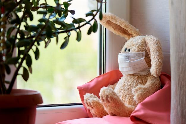 Ein ausgestopftes kaninchen in einer maske sitzt auf kissen in einer decke am fenster.