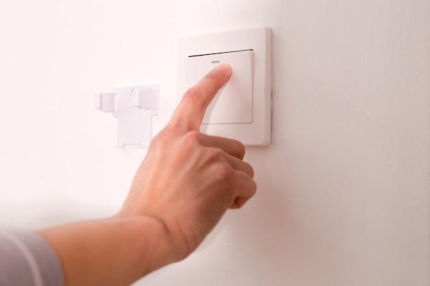 Ein- / ausschalten des an der wand montierten elektrischen lichtschalters.