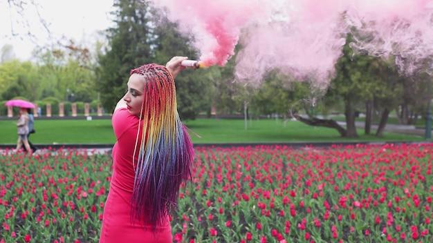 Ein außergewöhnliches mädchen in einem roten kleid mit make-up und farbigen zöpfen. süß lächeln und posieren in dickem rosa rauch im park im regen
