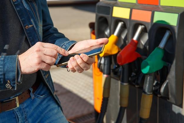 Ein auto tanken und mit der anwendung auf einem smartphone bezahlen.