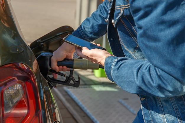 Ein auto tanken und mit der anwendung auf einem smartphone bezahlen