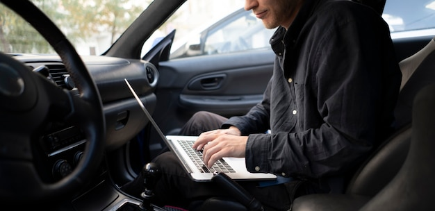 Ein automechaniker, der eine autodiagnose mit einem computer durchführt und nach einem prüfmotor sucht