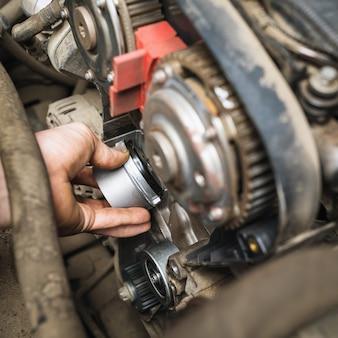 Ein automechaniker installiert eine zahnriemenspannrolle