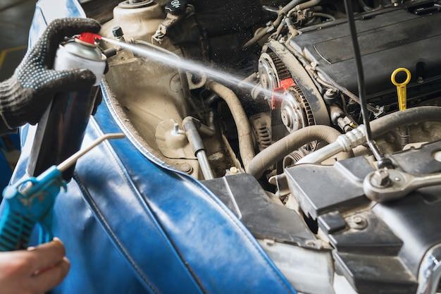 Ein automechaniker reinigt die fahrzeugkomponenten mit einem spray, bevor er den zahnriemen ersetzt