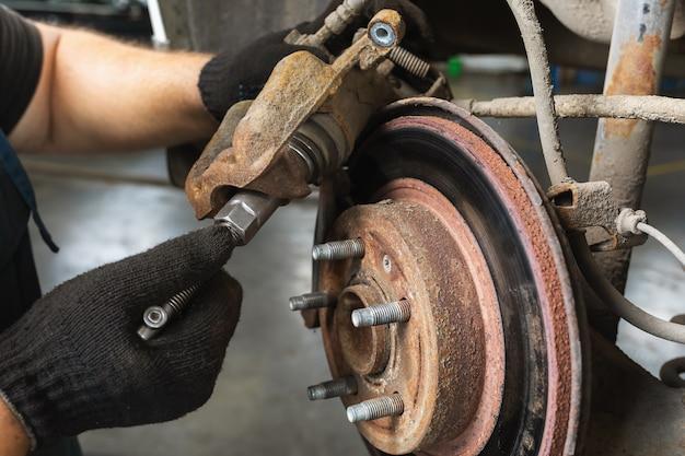 Ein automechaniker tauscht bremsbeläge aus, zieht eine schraube in einem bremssattel fest