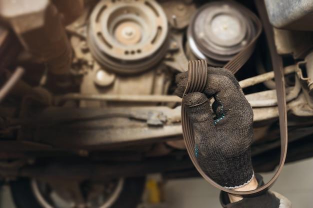 Ein automechaniker überprüft den zustand des generatorriemens auf verschiedene defekte
