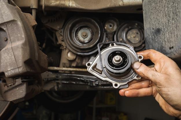 Ein automechaniker zeigt die ausgebaute alte motorpumpe