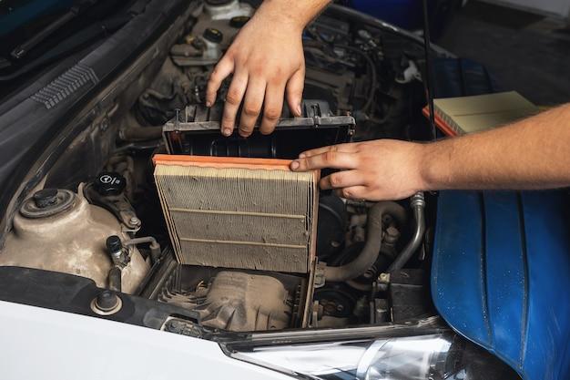 Ein automechaniker zeigt einen alten motorluftfilter