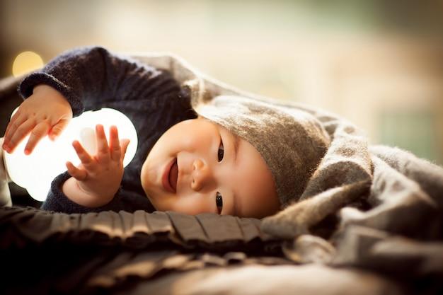 Ein baby, das auf einem grauen kissen liegt, genießt, die puppe zu sitzen und hell zu lächeln.