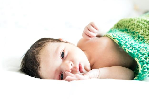 Ein baby im raupenkostüm liegt auf weißem hintergrund