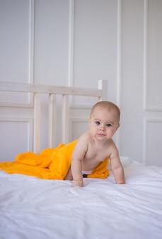 Ein baby in windel und mit einem orangefarbenen handtuch krabbelt auf dem bett. entwicklung des kindes