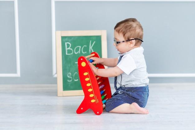 Ein baby mit brille und einer tafel, auf der bald zur schule steht, sitzt mit rechnungen