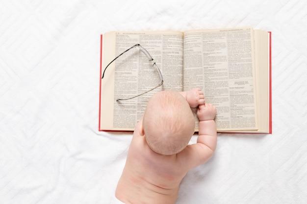 Ein baby mit einem buch, einer draufsicht, dem konzept der ausbildung und entwicklung