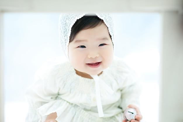 Ein baby mit einem weißen hintergrund und einem weißen hut spielt ein spiel.