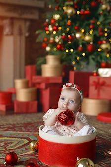 Ein baby sitzt in einer geschenkbox mit einer weihnachtskugel in der hand