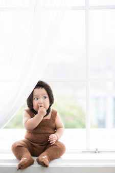 Ein baby sitzt vor einem weißen fenster und isst etwas und macht ein lustiges gesicht