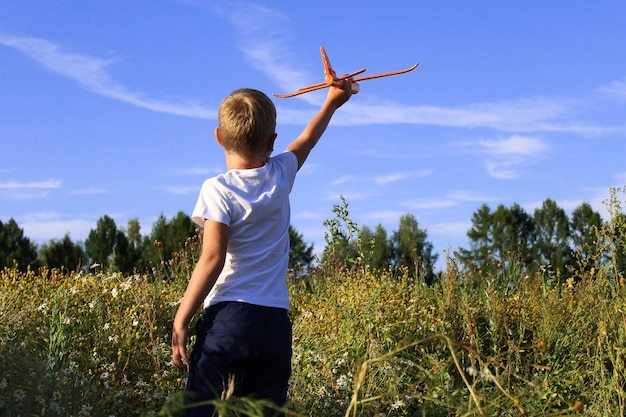 Ein baby startet ein spielzeugflugzeug in einem feld