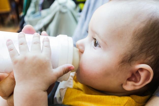 Ein baby trinkt eine babyflasche mit offenen augen