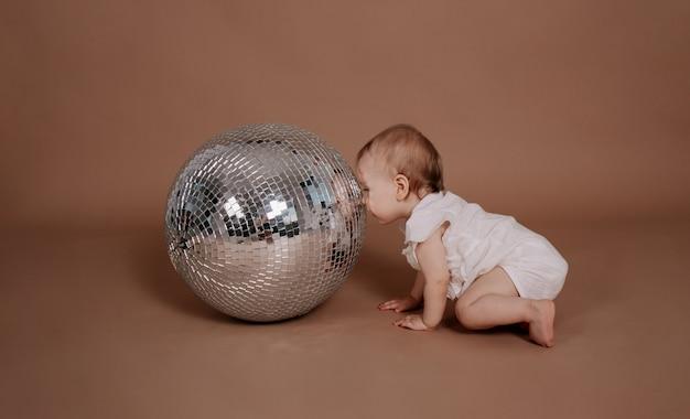 Ein babymädchen in einem weißen overall betrachtet eine silberne discokugel auf beigem hintergrund mit einem platz für text