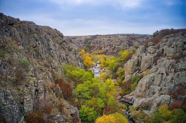 Ein bach fließt in den aktovsky canyon, ukraine. herbstliche bäume und große steinbrocken herum. panorama-drohnenaufnahme aus der luft