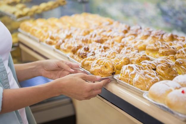 Ein bäcker präsentiert neue teller mit gebäck