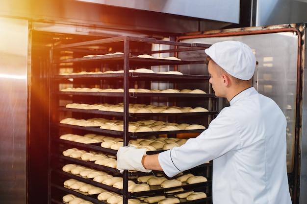 Ein bäcker trägt einen wagen mit einem backblech mit rohem teig in einen backofen