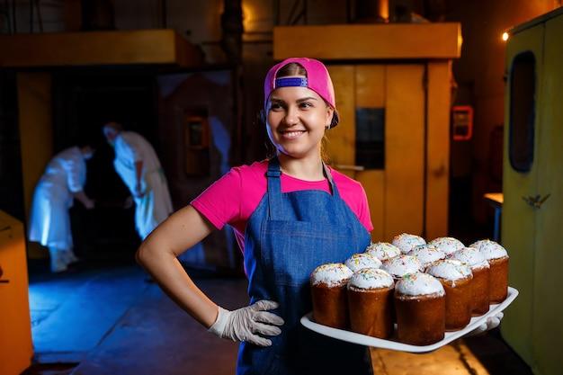 Ein bäckermädchen hält ein tablett mit heißem gebäck in der bäckerei. herstellung von backwaren. ein tablett mit frischem knusprigem gebäck.