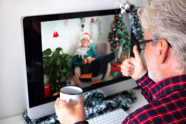 Ein bärtiger älterer mann im videoanruf für weihnachtsgrüße mit einer freundin, der glücklich lächelt und sich zu hause mit einer kaffeetasse entspannt