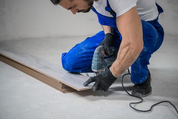 Ein bärtiger arbeiter in overalls markiert die tafel mit einem bleistift und benutzt eine stichsäge