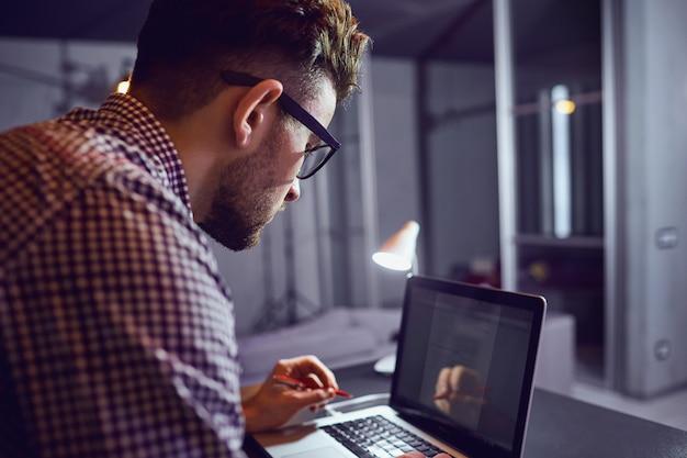 Ein bärtiger freiberufler des mannes mit einem laptop arbeitet
