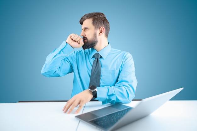 Ein bärtiger geschäftsmann an einem computer drückt seine faust an die lippen und macht eine geste des bedauerns, ein mann in blauem hemd und krawatte bedauert, was passiert ist