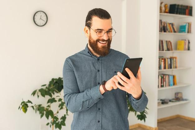 Ein bärtiger junger mann arbeitet im büro mit einer tablette