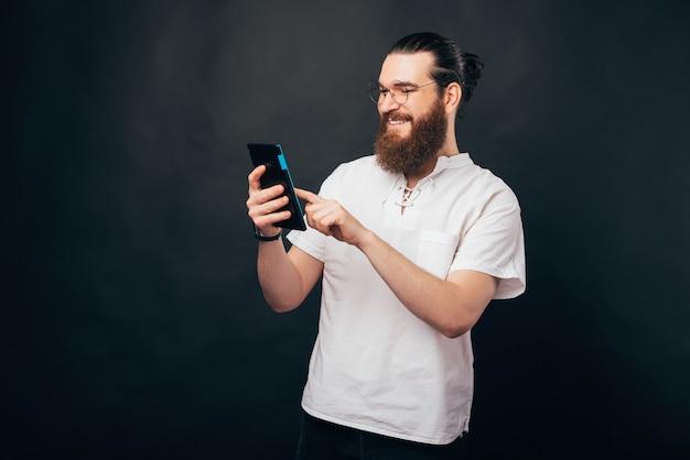 Ein bärtiger junger mann hält einen pc in der hand und tippt lächelnd ein