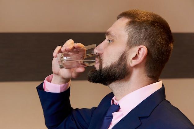 Ein bärtiger junger mann trinkt wasser aus einem glas.