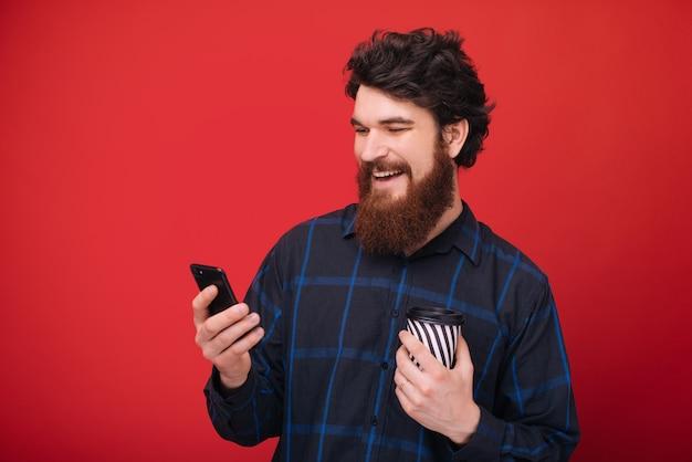 Ein bärtiger kerl, der ein smartphone benutzt, während er eine tasse mit kaffee über der roten wand hält