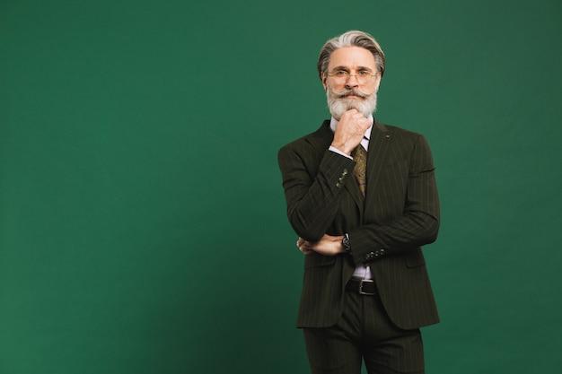 Ein bärtiger lehrer mittleren alters im anzug, der einen bart hält und an eine grüne wand mit kopierraum denkt
