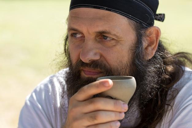 Ein bärtiger mann in einem bandana trinkt tee vor dem hintergrund der natur.