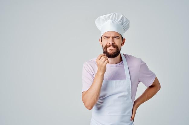 Ein bärtiger mann in einer kochuniform gestikuliert mit seinen händen die emotionen von profis