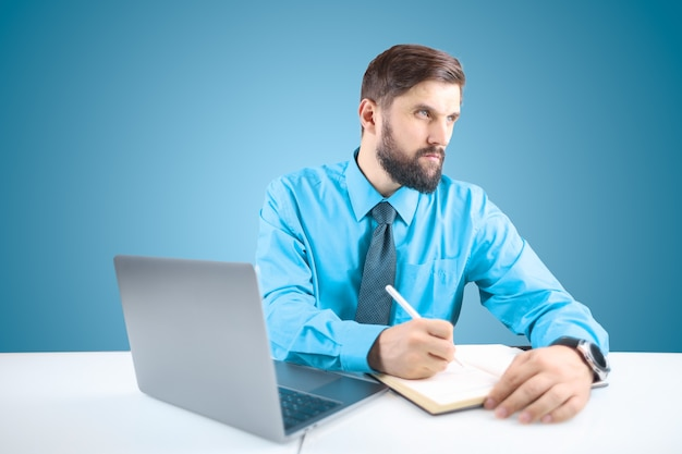 Ein bärtiger mann in hemd und krawatte sitzt an einem laptop und schreibt einen zeitplan in ein notizbuch