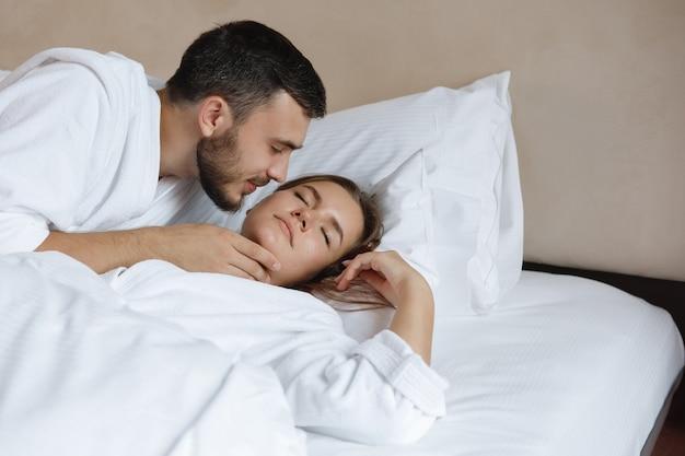Ein bärtiger mann küsst eine schlafende frau.