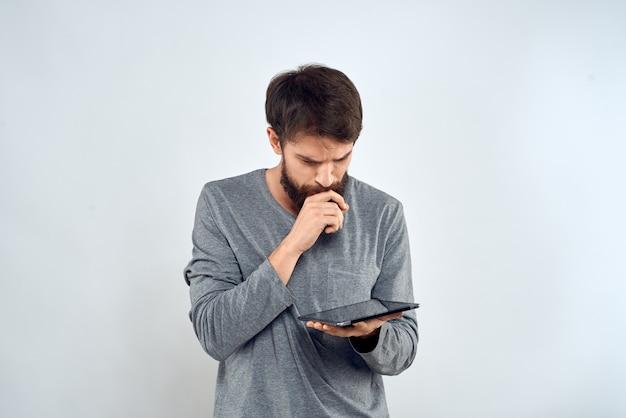 Ein bärtiger mann mit einer tablette in seinen händen ein grauer jackentechnologie-internetlichthintergrund. hochwertiges foto