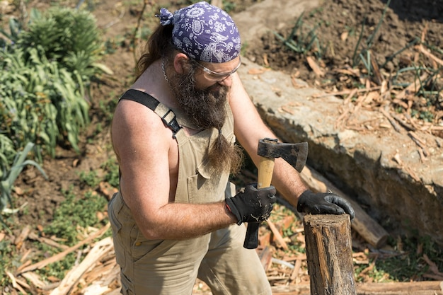 Ein bärtiger mann mittleren alters in einem kopftuch schneidet mit einer axt stämme. brutal im overall erledigt die harte arbeit