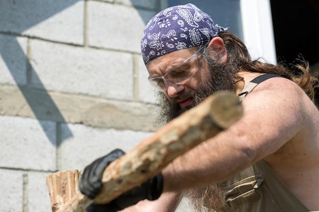 Ein bärtiger mann mittleren alters mit einem kopftuch schneidet mit einer axt baumstämme