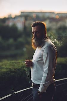 Ein bärtiger mann raucht eine zigarette gegen den sonnenuntergang