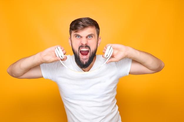 Ein bärtiger mann streckt die kopfhörer in verschiedene richtungen und schreit laut in die kamera.