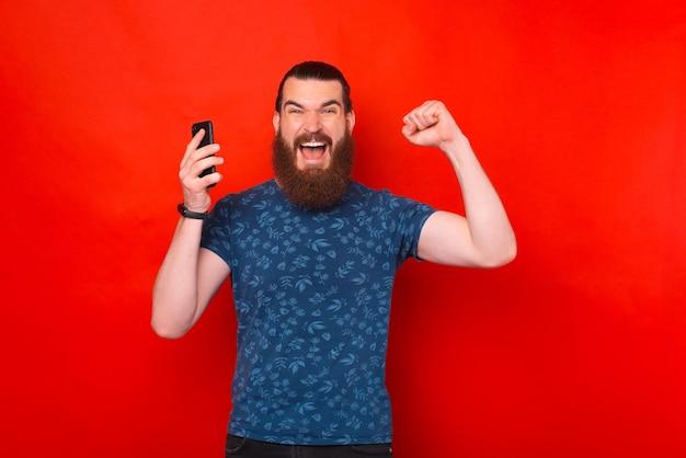 Ein bärtiger siegermann hält sein telefon und schreit in die kamera.