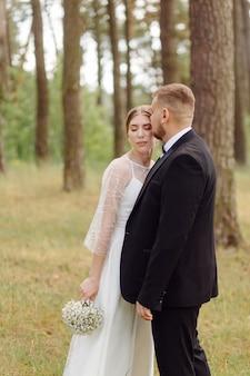 Ein bärtiger, stilvoller bräutigam im anzug und eine schöne blonde braut in einem weißen kleid mit einem strauß in den händen stehen und umarmen sich in der natur im kiefernwald.