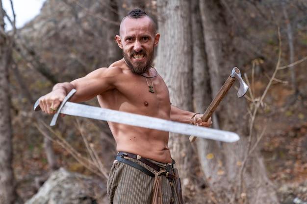 Ein bärtiger wikinger mit einem wütenden gesichtsausdruck steht in einer kampfhaltung und hält ein schwert und eine streitaxt