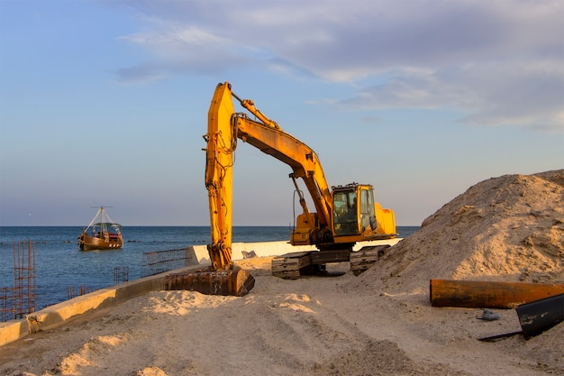 Ein bagger in der nähe des meeres gräbt sand, um einen strand an der küste zu bauen.